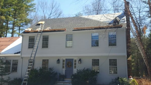 Roof Installation in Tewksbury MA. Three roofers laying new shingle on a roof in Tewksbury.